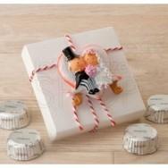Calamita sposi su panchina a cuore con scatola e cioccolatini