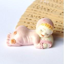 Statuetta in resina di bambino addormentato colore rosa